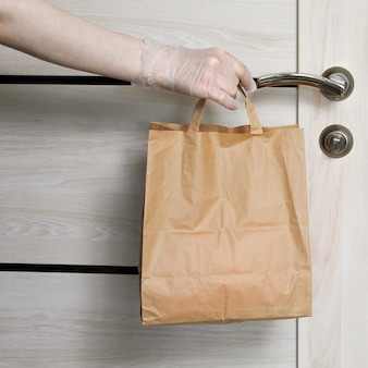 Levering tijdens de quarantaine. kruidenier winkelen bezorger geeft papieren zak met koopwaar, goederen en voedsel met beschermende handschoen als bescherming voor covid-19 coronavirus voorzorgsmaatregelen.
