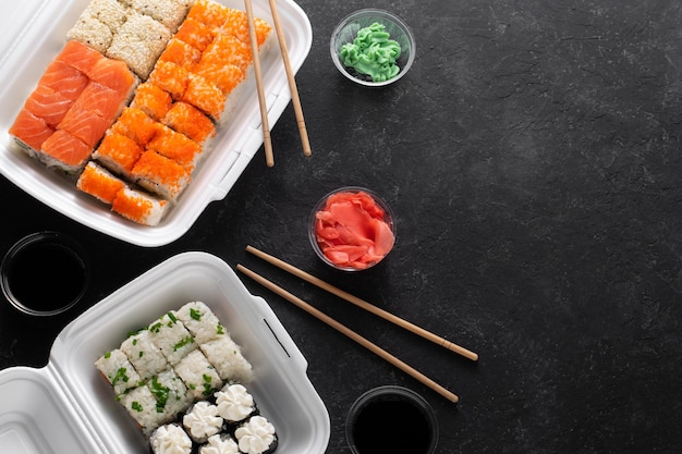 Levering van aziatische broodjes. fastfood in plastic dozen op een zwarte achtergrond