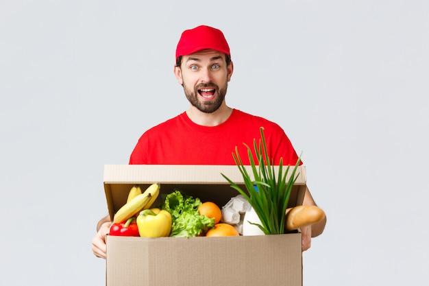 Levering van boodschappen en pakketten, covid-19, quarantaine en winkelconcept. de glimlachende knappe gebaarde koerier in rood uniform, brengt voedselpakket, kruidenierswinkelorde aan cliënt in doos, kijkt geamuseerd