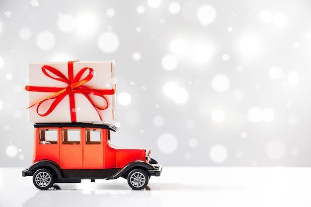 Levering van cadeaus voor de vakantie. retro speelgoedauto met een geschenkdoos op het dak.