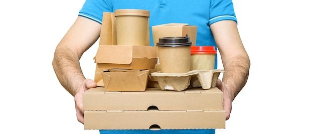 Levering van fastfood. bezorger draagt diverse papieren containers voor afhaalmaaltijden geïsoleerd op wit.
