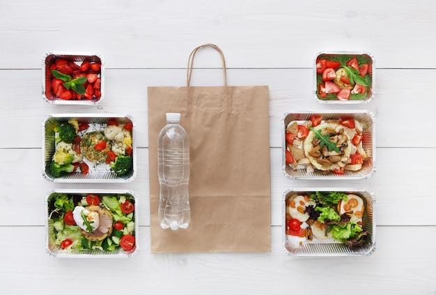 Levering van gezonde voeding, dagelijkse maaltijden en snacks. voeding, groenten, vlees, waterfles en fruit in foliedozen en pakpapier. bovenaanzicht, plat lag op wit hout met kopie ruimte