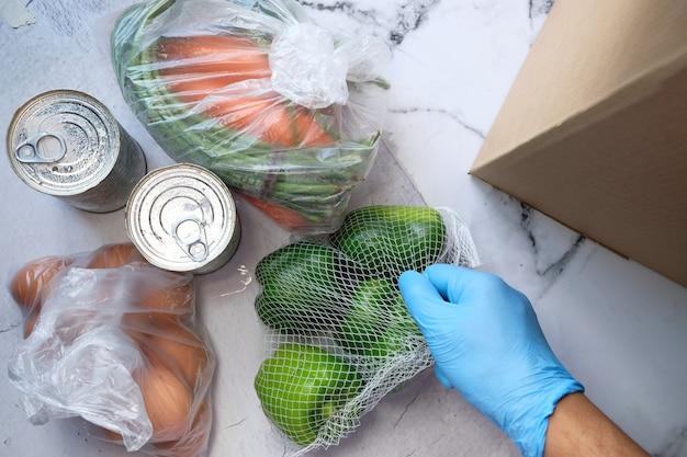 Levering van goederen aan de deur. orderverzamelaar die voedsel verpakt in kartonnen dozen.