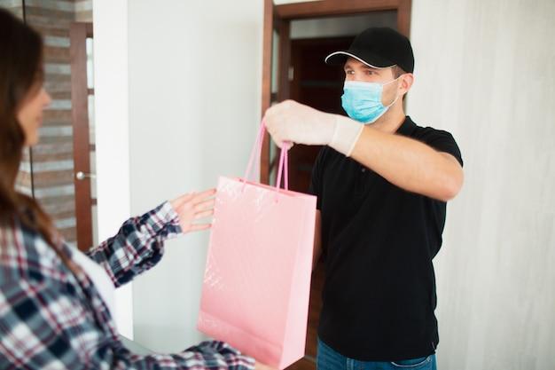 Levering van goederen en aankopen aan huis. de koerier of bezorger geeft het pakket met de goederen door aan een jonge vrouw. ze betaalt zijn werk met een creditcard. hij draagt een masker