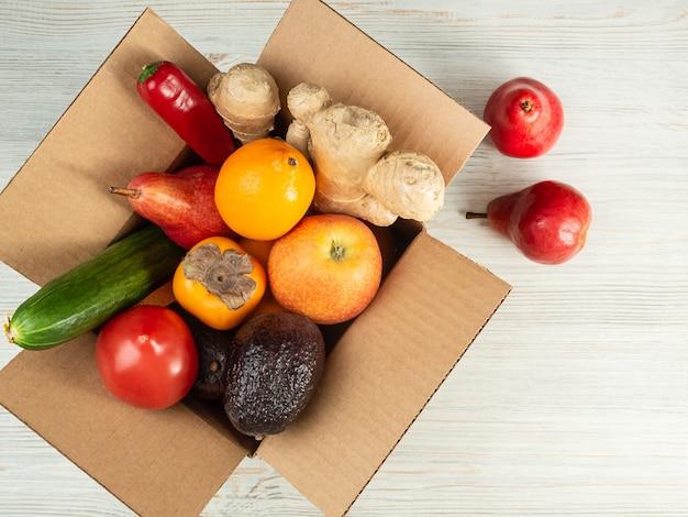 Levering van groenten en fruit in een cortondoos, de doos is open, op een houten tafel, bovenaanzicht.
