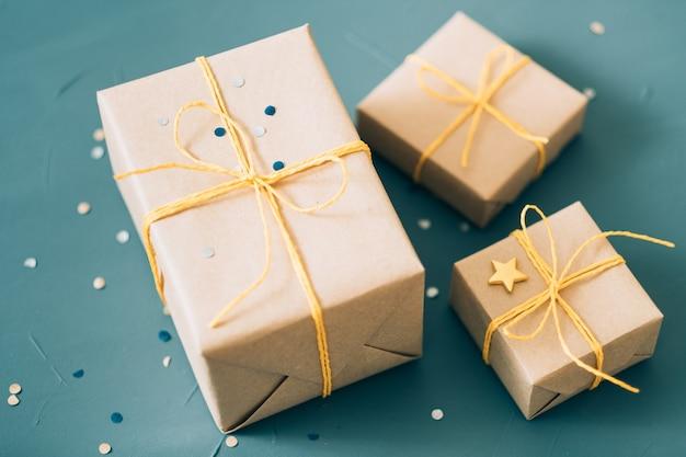 Levering van kerstcadeautjes. selectie van geschenkdozen verpakt in knutselpapier en vastgebonden met geel touw. viering dankbaarheid en felicitatie concept.