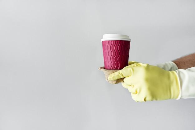 Levering van koffie. de handen van de koerier in beschermende handschoenen houden een ambachtelijk glas met koffie vast. koffie om mee te nemen. blijf thuis. coronavirus, quarantaine, isolatie