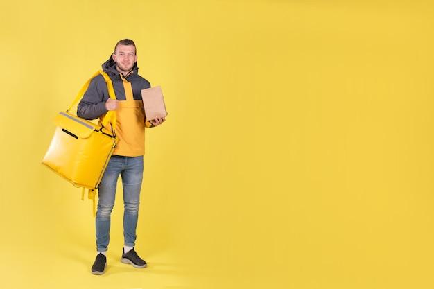 Levering van voedsel jonge man in een gele jas