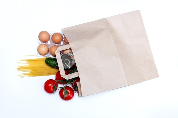 Levering van voedsel papieren zak met verse producten, pasta, ingeblikt voedsel, groenten, boter, eieren. donaties