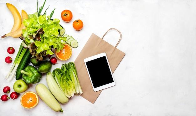 Levering voedsel concept. verschillende groenten tablet computer papieren boodschappentas op wit