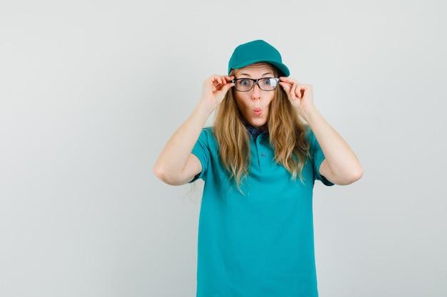 Levering vrouw bril in t-shirt, pet en op zoek grappig