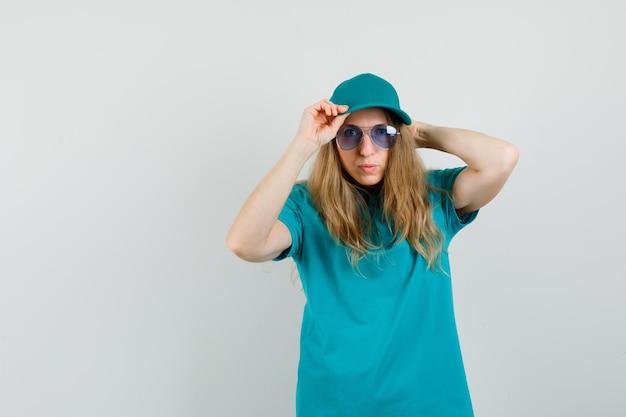 Levering vrouw camera kijken tijdens het aanpassen van pet in t-shirt, pet en ziet er cool uit