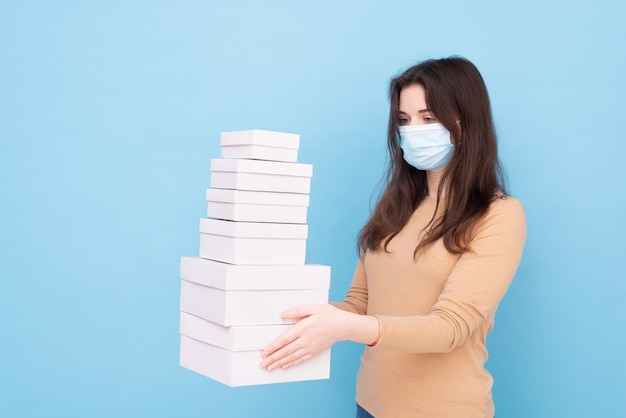 Levering vrouw draagt een medisch masker en houdt close-up van vele witte papieren dozen