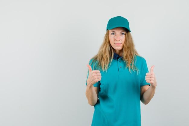Levering vrouw dubbele duimen opdagen in t-shirt, pet en op zoek tevreden.