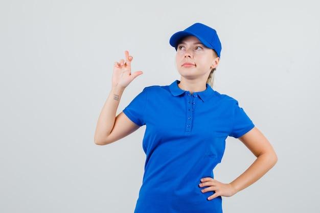 Levering vrouw houdt vingers gekruist in blauw t-shirt en pet en kijkt hoopvol