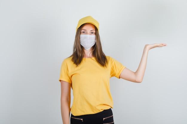 Levering vrouw iets tonen met hand in t-shirt, broek, pet en masker