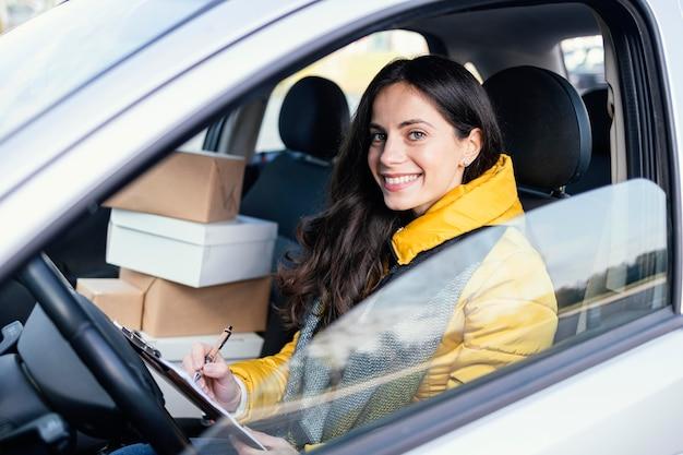 Levering vrouw in auto met pakket