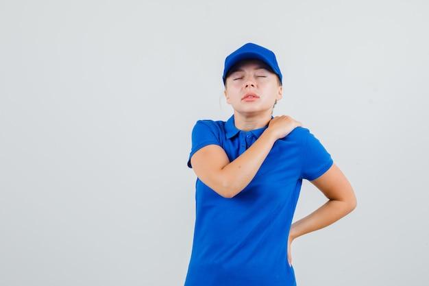 Levering vrouw in blauw t-shirt en pet die aan schouderpijn lijdt en er moe uitziet