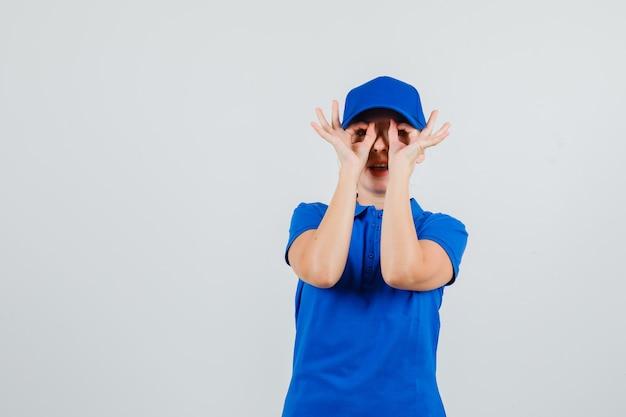 Levering vrouw in blauw t-shirt en pet met bril gebaar en op zoek grappig