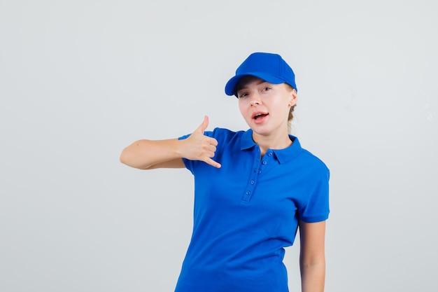 Levering vrouw in blauw t-shirt en pet met telefoongebaar en op zoek zelfverzekerd
