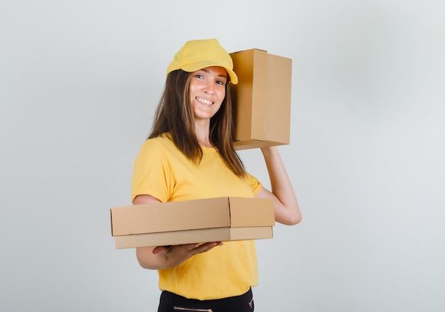Levering vrouw in geel t-shirt, broek, pet met kartonnen dozen en glimlachen