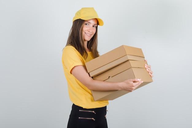 Levering vrouw in geel t-shirt, broek, pet met kartonnen dozen en op zoek blij