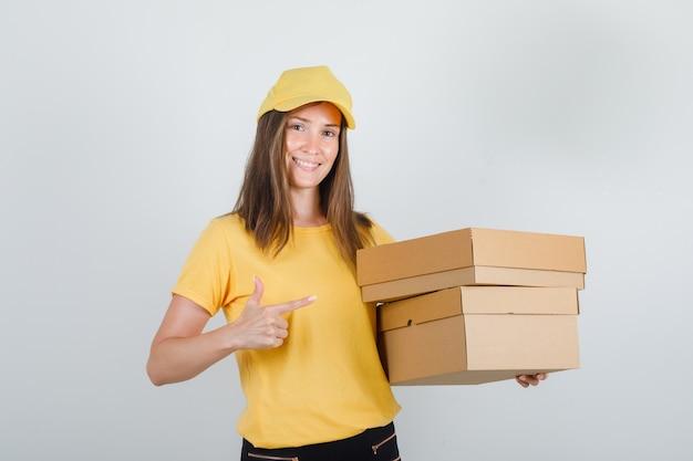 Levering vrouw in geel t-shirt, broek, pet wijzende vinger naar kartonnen dozen en kijkt blij