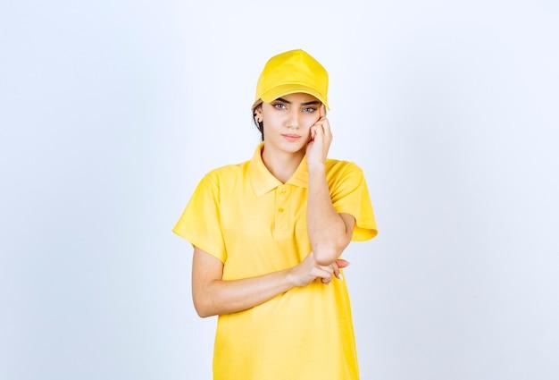 Levering vrouw in gele uniform staan en denken.