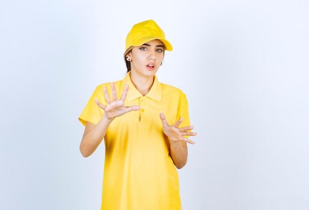 Levering vrouw in gele uniform staan en kijken naar de camera.