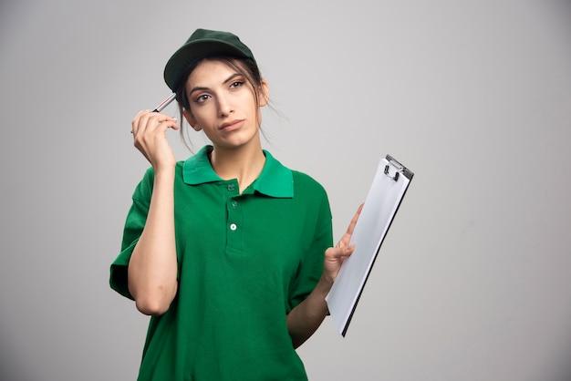 Levering vrouw in groen uniform klembord houden.