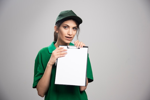 Levering vrouw in groen uniform klembord houden. Gratis Foto