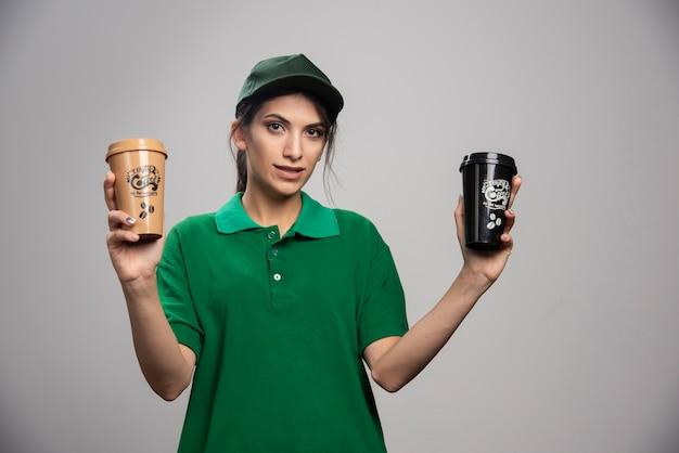Levering vrouw in groene uniform poseren met heerlijke koffie.