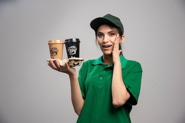 Levering vrouw in groene uniforme status met kopjes koffie.