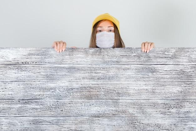 Levering vrouw in pet, masker gluren achter een houten bord