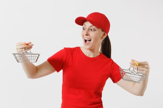 Levering vrouw in rode uniform geïsoleerd op een witte achtergrond. vrouwelijke koerier of dealer in pet, t-shirt, jeans met metalen boodschappenmand om te winkelen in de supermarkt. kopieer ruimte voor advertentie.