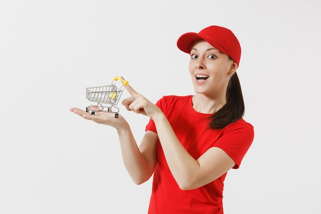 Levering vrouw in rode uniform geïsoleerd op een witte achtergrond. vrouwelijke koerier of dealer in pet, t-shirt, spijkerbroek met supermarkt boodschappenwagentje om te winkelen op palm. kopieer ruimte voor advertentie.