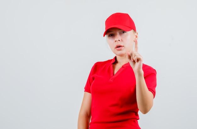 Levering vrouw in rood t-shirt en pet die naar boven wijst en peinzend kijkt