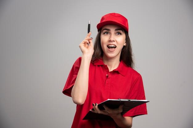 Levering vrouw in rood uniform gelukkig gevoel op grijze muur.