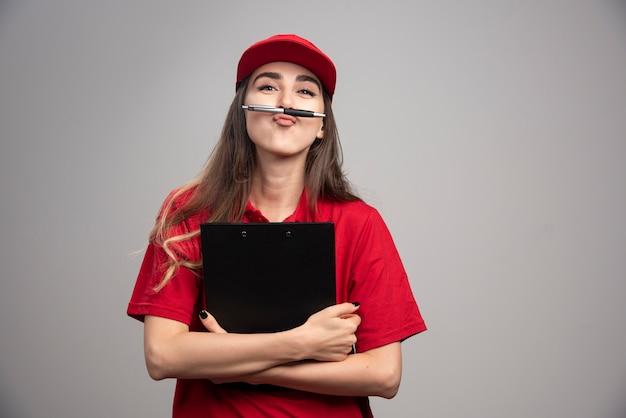 Levering vrouw in rood uniform klembord en pen.