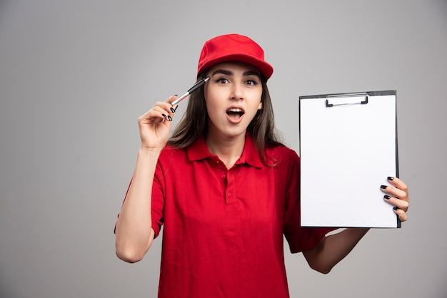 Levering vrouw in rood uniform klembord houden en praten.