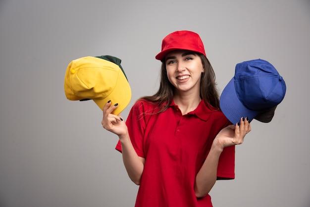 Levering vrouw in rood uniform met kleurrijke caps.