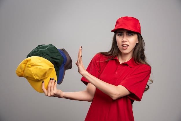 Levering vrouw in rood uniform wegblijven van kleurrijke caps.