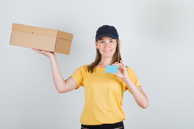 Levering vrouw in t-shirt, broek, pet met kartonnen doos en blauwe kaart