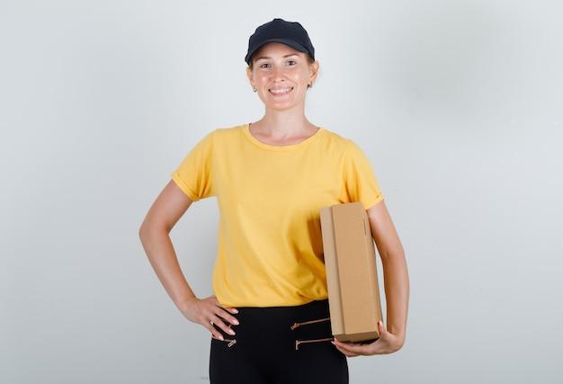 Levering vrouw in t-shirt, broek, pet met kartonnen doos en glimlachen