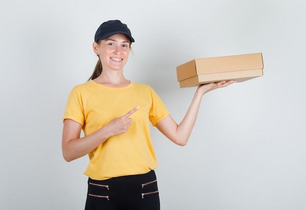 Levering vrouw in t-shirt, broek, pet wijzende vinger naar kartonnen doos en ziet er vrolijk uit