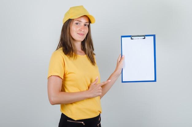 Levering vrouw in t-shirt, broek, pet wijzende vinger naar klembord en ziet er vrolijk uit