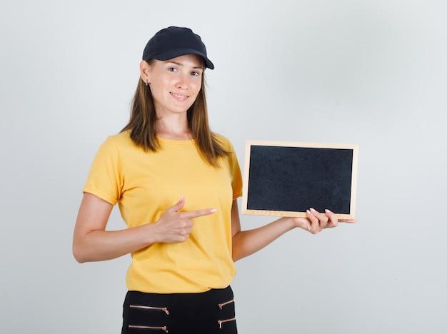 Levering vrouw in t-shirt, broek, pet wijzende vinger naar schoolbord en kijkt blij