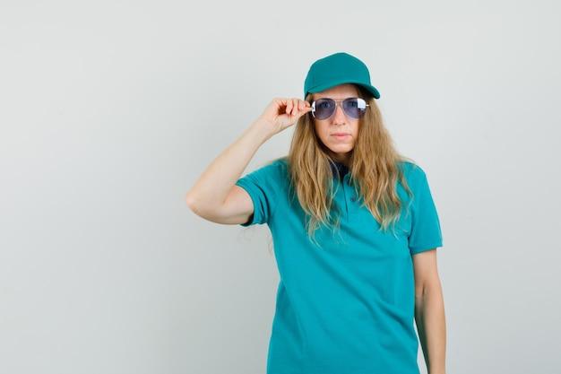 Levering vrouw in t-shirt, pet camera kijken door een bril en gericht kijken