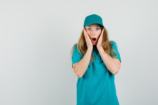Levering vrouw in t-shirt, pet hand in hand in de buurt van open mond en op zoek geschokt