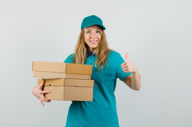 Levering vrouw in t-shirt, pet met kartonnen dozen met duim omhoog en op zoek blij